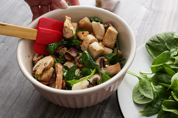 Mixing chicken and mushrooms together.