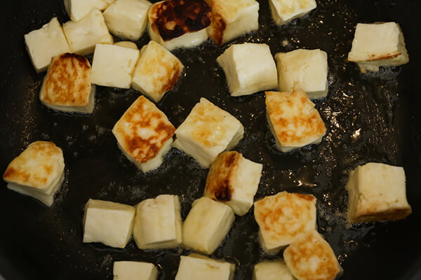 Halloumi frying in a pan.