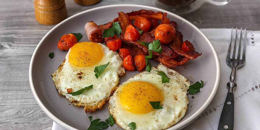 Fried eggs with bacon and cherry tomatoes.