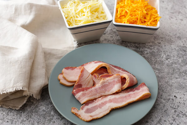 Cheese in bowls and raw bacon on a plate.