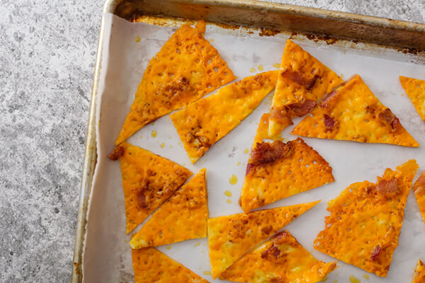 Cheese chip triangles on a baking tray.