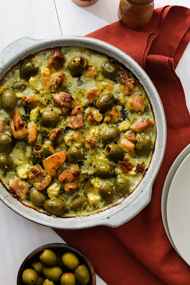Low carb pesto chicken, feta, and olive casserole on a table.