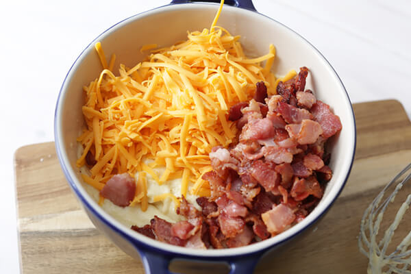 Bread batter in a bowl with cheese and bacon on top.