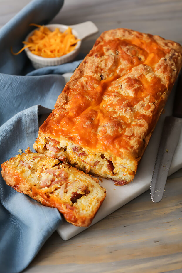 Finished keto cheesy bacon bread with slice cut off the end, revealing the tasty inside!