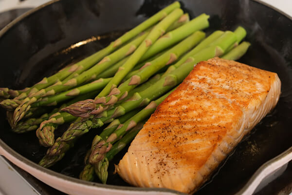 Salmon and asparagus cooking in a pan.