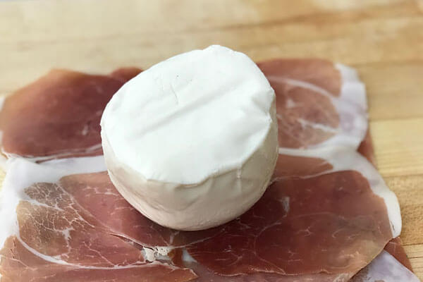 Prosciutto slices with mozzarella ball on top.