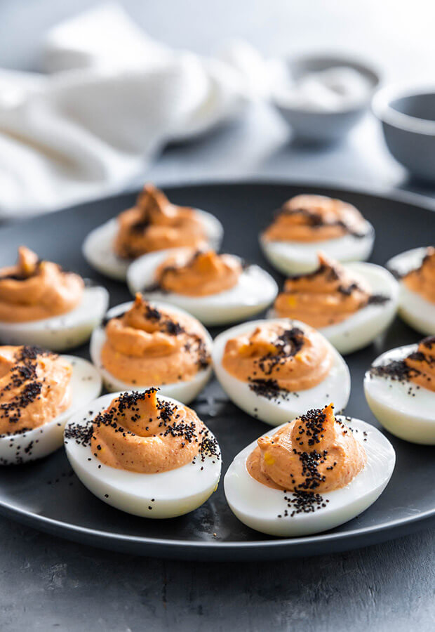 Spicy keto deviled eggs made with red curry paste and topped with poppy seeds.