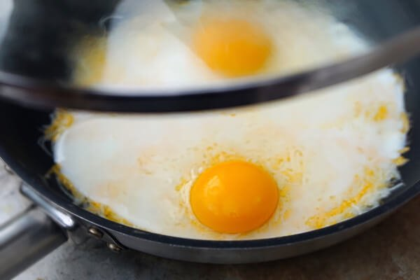 Covering eggs in a skillet.