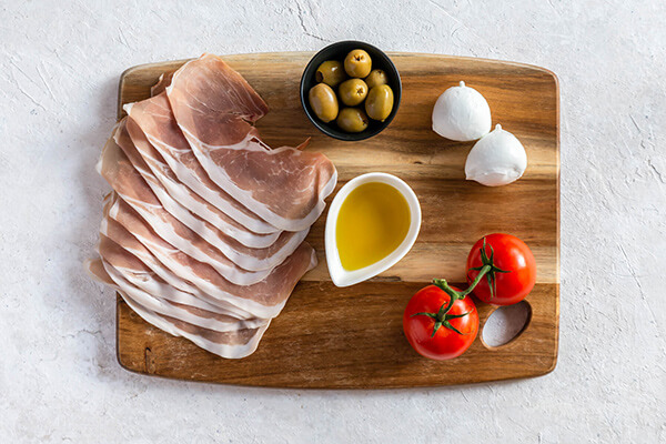 Prosciutto, olives, eggs, and tomatoes on a cutting board.